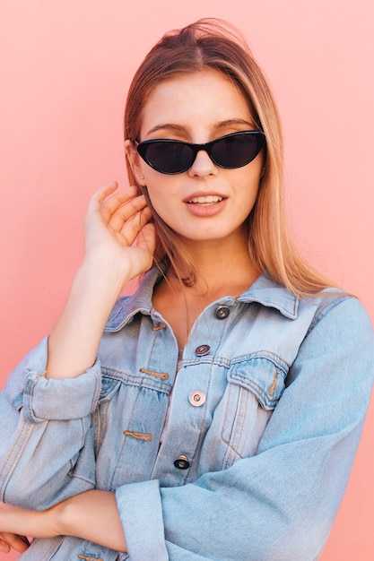 Stylish young woman in blue denim shirt standing against pink backdrop Free Photo