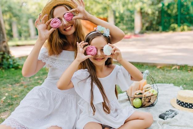 La giovane donna alla moda è venuta con la figlia carina al parcheggio per trascorrere il fine settimana insieme. ritratto all'aperto della ragazza dai capelli castani che scherza con la madre mentre mangia i biscotti sulla coperta. Foto Gratuite