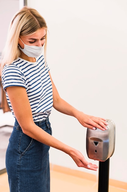 Stylish young woman disinfecting hands Free Photo