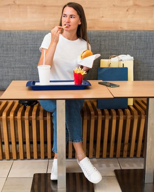 Стильная молодая женщина ест фаст-фуд Бесплатные Фотографии