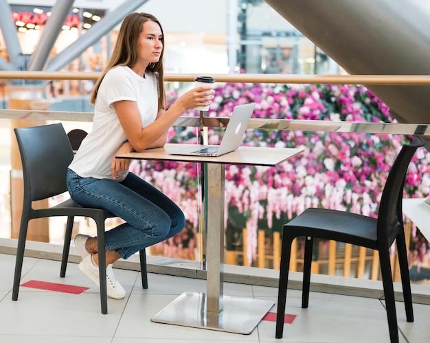 コーヒーを楽しむスタイリッシュな若い女性 無料写真
