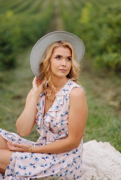 ローズブルーのヴィンテージのドレスと帽子のグリーンフィールドでポーズのスタイリッシュな若い女性 無料写真