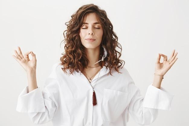 Stylish young woman meditating, practice yoga breathing Free Photo