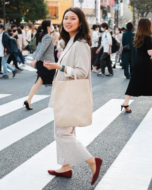 Una giovane donna alla moda che propone sulla strada Foto Gratuite
