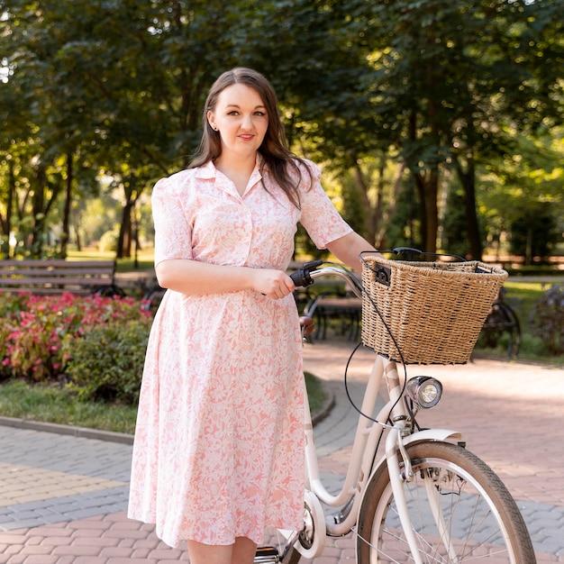 Стильная молодая женщина позирует с велосипедом Premium Фотографии