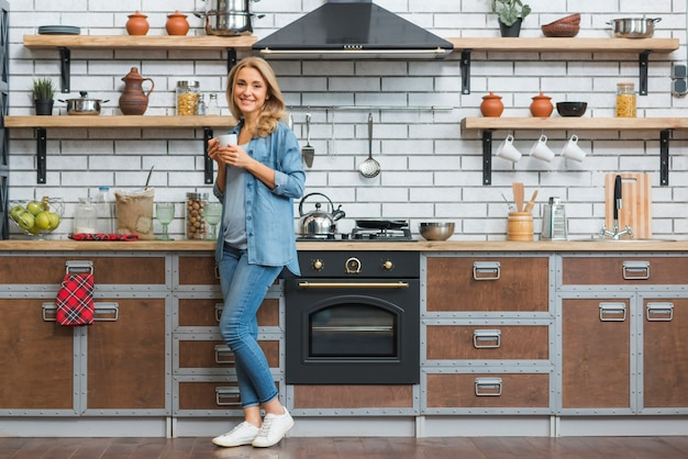 Stylish young woman standing in modular kitchen holding cup of coffee in hand Free Photo