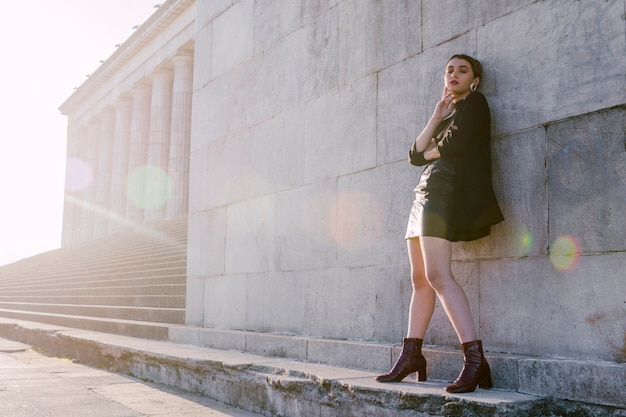 Stylish young woman standing in wall with sunlight Free Photo