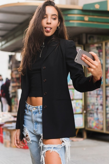 Stylish young woman sticking her tongue out while taking selfie on mobile phone Free Photo
