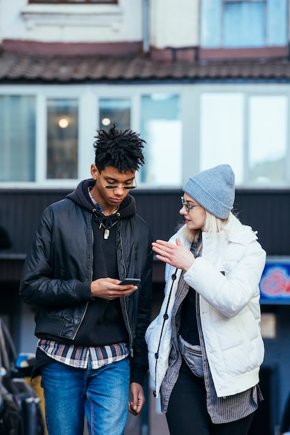 Stylish young woman talking to her handsome boyfriend using mobile phone Free Photo