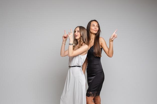 Стильные молодые женщины в вечерних платьях, указывающие на пустые места для вашего контента на сером студийном фоне Бесплатные Фотографии