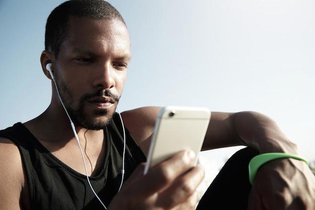 水の近くの階段に座って音楽を聴くスタイリッシュな若者。デバイスで音楽やテキストメッセージを楽しんでいる緑のフィットネストラッカーと黒いノースリーブの孤独なアフリカ系アメリカ人の男。 無料写真