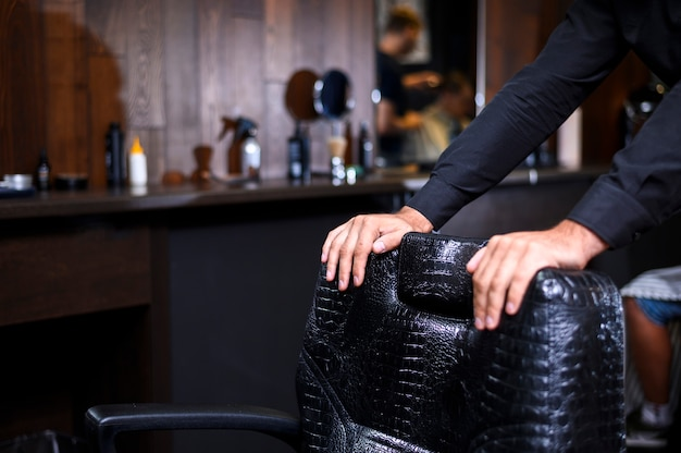 Stylist leaning on barber shop leather chair Free Photo