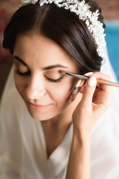 Stylist makes makeup bride on the wedding day Premium Photo