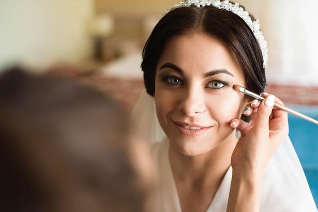 Stylist makes makeup bride on the wedding day Premium Photo