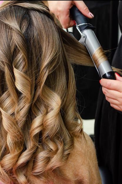 Stylist making a hairdo with hair curler. beauty salon concept Premium Photo