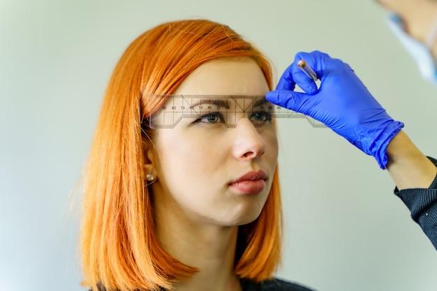 Стилист измеряя брови с линейкой на рыжеволосой женщине. микропигментация, работа в салоне красоты. Premium Фотографии