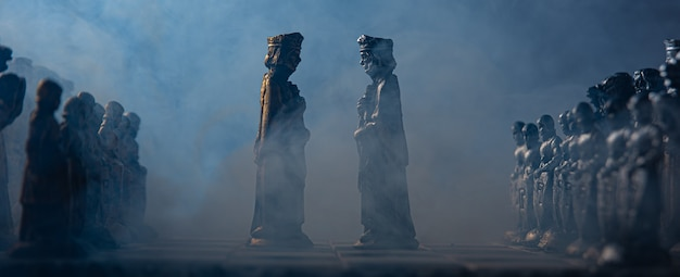 Stylized chess pieces on a board with black background, smoke and selective focus Premium Photo