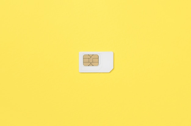Subscriber identity module. white sim card on yellow background Premium Photo