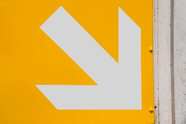 Freccia bianca del sottopassaggio su fondo giallo Foto Gratuite