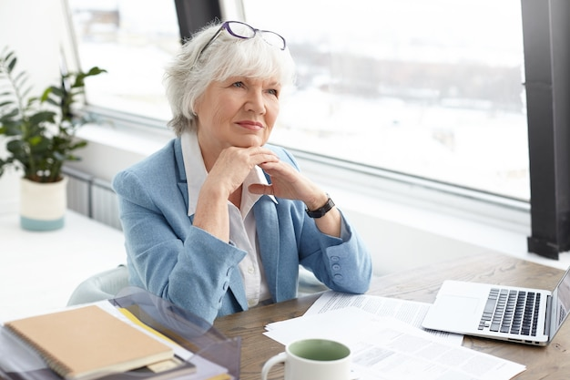 Succesfful skilled attractive elderly female editor of popular fashion magazine sitting at her workplace with papers, mug and open portable computer, clasping hands, having pensive facial expression Free Photo