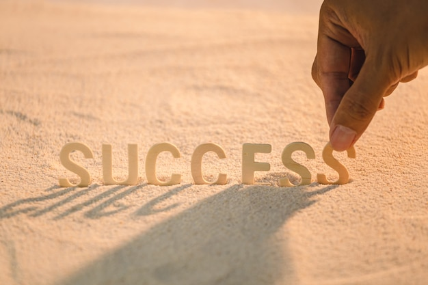 Success - concept for business motivation with wooden alphabet put on the sand beach.  inspirational quote. motivational words Premium Photo