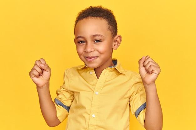 Concetto di successo, trionfo, gioia e felicità. adorabile carino eccitato ragazzino afroamericano con un'espressione facciale estatica felicissima, sorridente, pugni serrati, ricezione di buone notizie positive Foto Gratuite