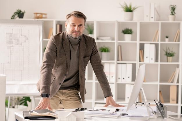 Успешный и уверенный в себе архитектор в строгой одежде, склонившись над столом с монитором компьютера и канцелярскими принадлежностями Premium Фотографии