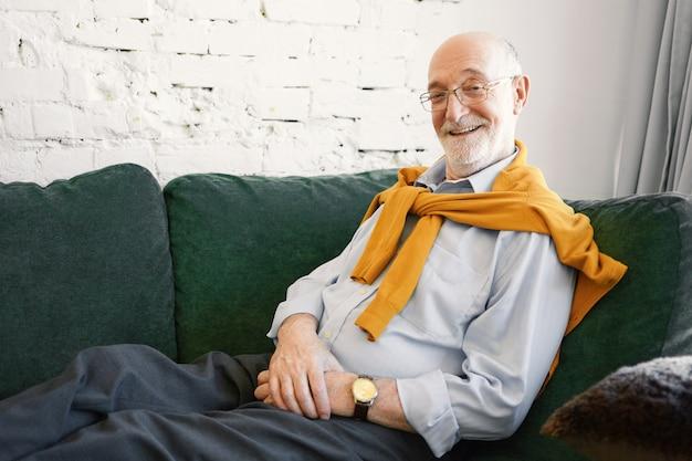 Успешный привлекательный пожилой бизнесмен в очках, строгой рубашке и джемпере на шее, сидящий на диване в своем офисе, с лучезарной улыбкой, счастливый после заключения хорошей сделки Бесплатные Фотографии