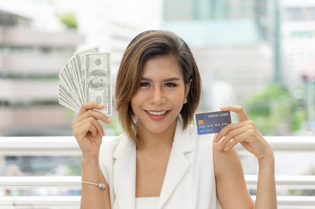 Successful beautiful asian business woman holding money us dollar bills and credit card in hand Free Photo