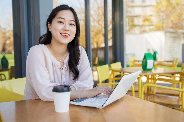 Successful blogger working on article in street cafe Free Photo