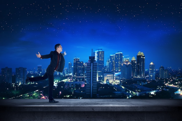 Successful business man on the rooftop at night time Premium Photo