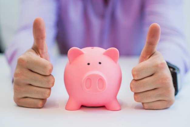 Successful business man with piggy bank holding thumbs up in office Free Photo