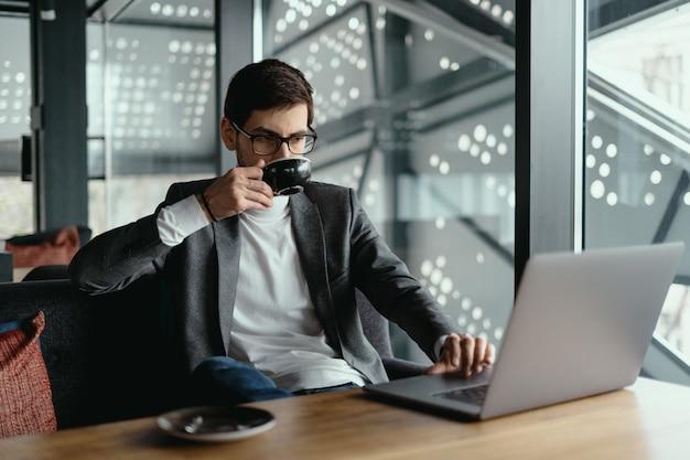 コーヒーを飲みながらノートパソコンで作業する成功するビジネス人 無料写真