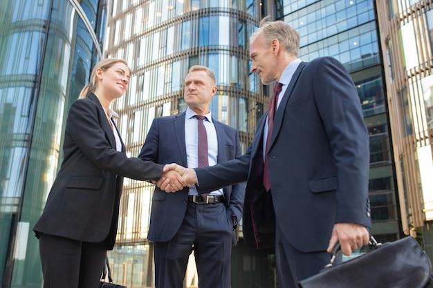 Uomini d'affari di successo che si incontrano in città, si stringono la mano vicino all'edificio per uffici. inquadratura dal basso. comunicazione e concetto di partenariato Foto Gratuite