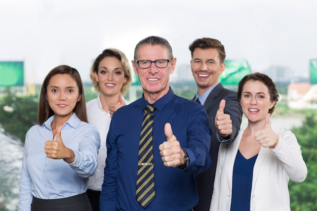 Successful business team with thumbs up smiling Free Photo