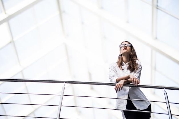 白いtシャツを着たモダンなオフィスセンターのバルコニーを見渡して立っている成功したビジネス女性 無料写真