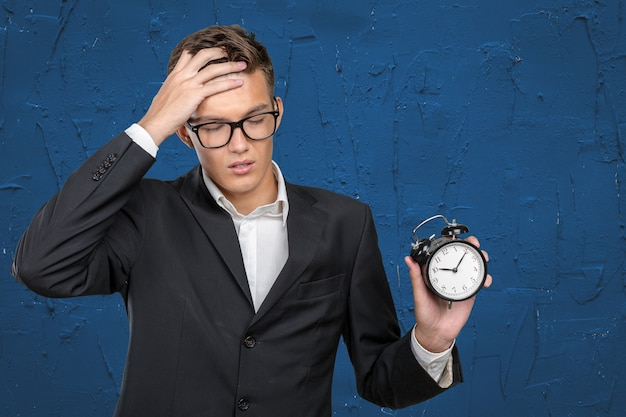 Successful businessman in formal wear pointing at clock Premium Photo