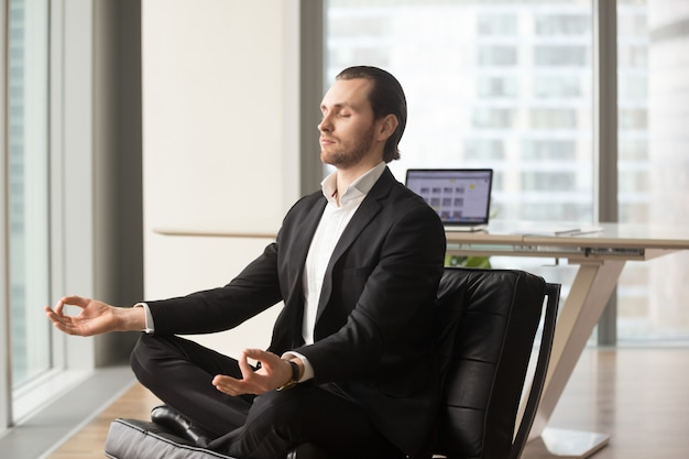 Successful businessman meditating at workplace Free Photo