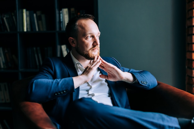 Successful businessman in a suit sits in a chair with folded arms and looks out the window. Premium Photo