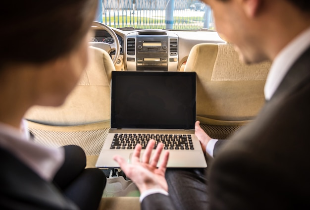 Successful businesspeople at a meeting sitting in the car. Premium Photo