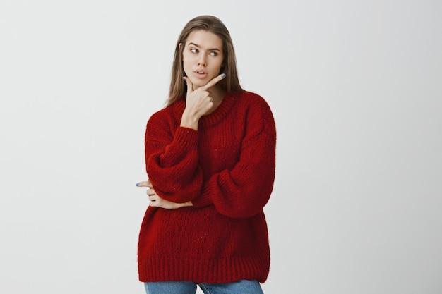 厄介な状況から逃れる方法を決定する成功した実業家。赤いルーズセーターで深刻な豪華なヨーロッパの女性のショット 無料写真