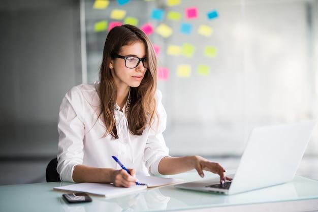 흰 옷을 입고 그녀의 사무실에서 랩톱 컴퓨터에서 열심히 일하는 성공적인 사업가 무료 사진