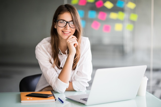성공적인 사업가 랩톱 컴퓨터에서 작업하고 흰 옷을 입은 그녀의 사무실에서 새로운 아이디어에 대해 생각합니다. 무료 사진