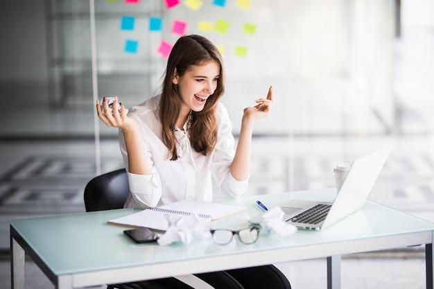 白い服を着た彼女のオフィスでラップトップコンピューターで作業して成功した実業家 無料写真