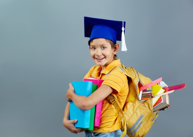 Successful child with graduation cap and backpack full of books Free Photo