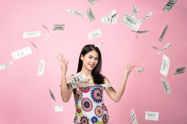 Successful concept, portrait of young woman with falling dollars banknotes in the ai Premium Photo