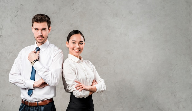 Successful and confident young businessman and businesswoman standing against grey wall Free Photo