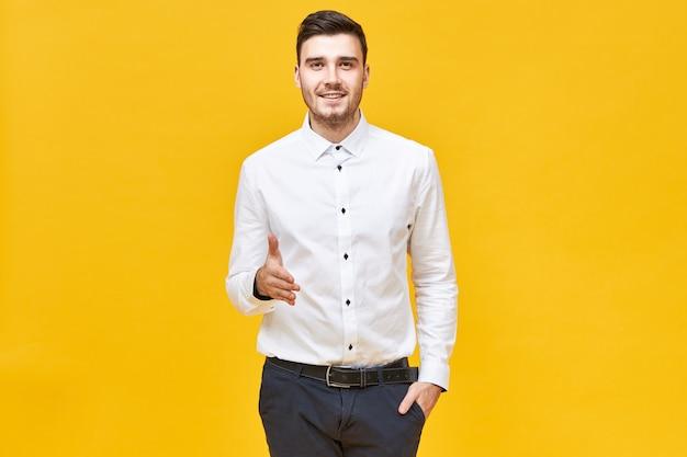 Giovane fiducioso di successo in camicia bianca formale e pantaloni classici che sorride e tende la mano per stringere la tua, facendo un gesto di benvenuto e di saluto, pronto a fare un accordo Foto Gratuite