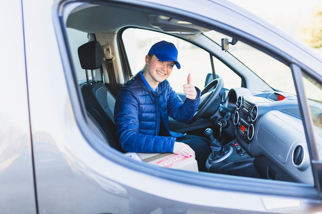 Successful delivery worker showing thumb up Free Photo