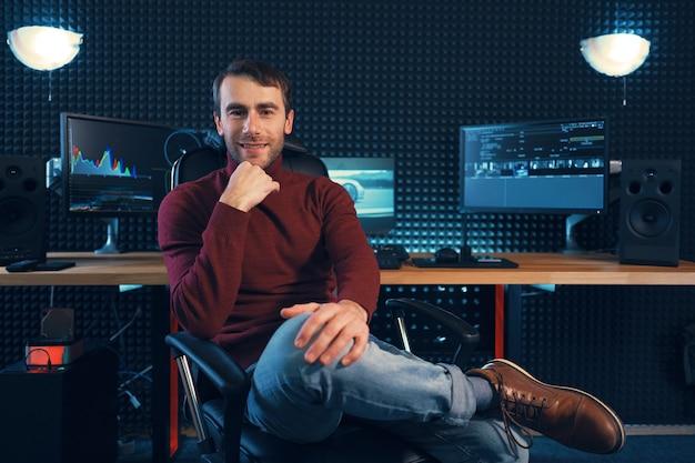 Успешный дизайнер или редактор сидит ногой к ноге в кожаном кресле и смотрит в камеру, с мониторами и звукоизоляционной стеной на заднем плане с местом для копирования Premium Фотографии